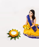 Indian woman making rangoli using flowers. Indian woman or young girl making floral or flower rangoli for diwali or onam, isolated over white background Royalty Free Stock Images
