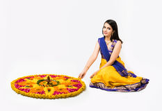 Indian woman making rangoli using flowers. Indian woman or young girl making floral or flower rangoli for diwali or onam, isolated over white background Stock Images