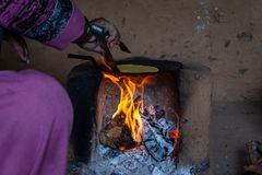 Indian woman making Roti in traditional stove chulha under tough conditions stock image