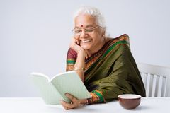 Indian woman. Mature Indian woman reading book and smiling Stock Image