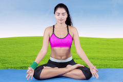 Indian woman meditating at field. Beautiful indian woman doing meditation while wearing sportswear and sitting on mattress at field Royalty Free Stock Images