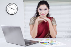 Indian woman in office with laptop and financial chart Royalty Free Stock Photo