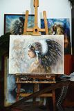 Indian woman in painting atelier on stand with harp and paintings. Beautiful airbrush painting of a young native indian woman in painting atelier Royalty Free Stock Image