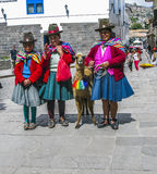 Indian woman pose with a lama for tourists in Cuzco Royalty Free Stock Images