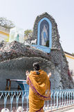 Indian woman praying in front of a Maria statue next to the Immaculate Conception Cathedral in Pondicherry Stock Photo