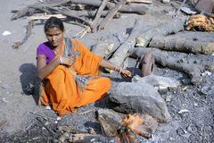 Indian woman prepaing sheeps head for cooking on B Royalty Free Stock Image