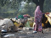 Indian woman in a purple saree passes by made-up tents in Bihar. stock images