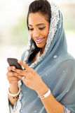 Indian woman reading emails. Smiling indian woman in traditional clothes reading emails on smart phone Royalty Free Stock Image
