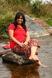 Indian woman in red dress sitting on a rock Stock Image