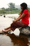 Indian woman in red dress sitting on a rock Stock Images