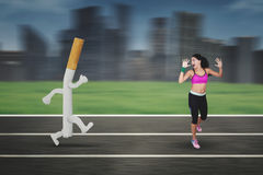 Indian woman running away from a cigarette Stock Photo