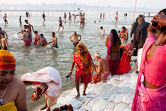 Indian woman in sari collect holy water. Indian woman collect holy water from the Sangam - confluence of Ganges and Yamuna - at the biggest festival in the world Royalty Free Stock Images