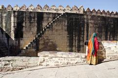 Indian woman with sari and fort wall in Jodphur Royalty Free Stock Images