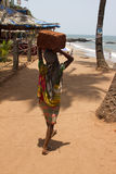 The Indian woman in a sari stones for building on the head on a beach. India Goa Stock Photography