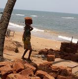 The Indian woman in a sari stones for building on the head on a beach. India Goa Royalty Free Stock Photo