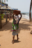 The Indian woman in a sari stones for building on the head on a beach. India Goa Royalty Free Stock Photography