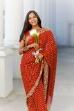 Indian Woman in Sari Walking with Flowers Stock Photos