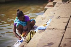 Indian woman in sari washing clothes in the river Royalty Free Stock Images