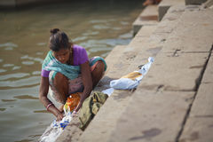 Indian woman in sari washing clothes in the river Stock Image