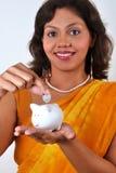 Indian woman saving money in piggy bank Stock Photo