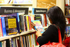 Indian Woman Selecting Management Books Royalty Free Stock Image