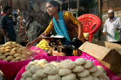 Indian woman seller. An Indian woman displayed different homemade sweets and cookies for sell on a road side stall Royalty Free Stock Images
