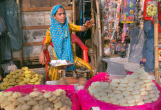 Indian woman seller. An Indian woman displayed different homemade sweets and cookies for sell on a road side stall Stock Photos