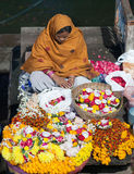 Indian woman selling pooja items in Varanasi, India. VARANASI, INDIA - JANUARY 3, 2016: Indian woman selling pooja items for the offering - diyas, orange and Stock Images