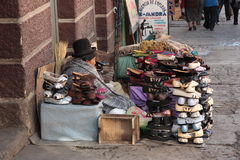 Indian woman sells shoes in street, La Paz, Bolivia Royalty Free Stock Photo
