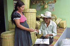 Indian woman sells wicker baskets to shopkeeper Royalty Free Stock Images