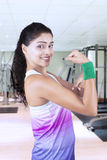 Indian woman shows bicep in fitness center Stock Photos