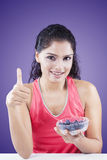 Indian woman shows thumb up with blueberries Stock Photo