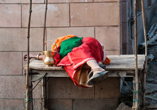 Indian woman sleeping on wooden table in the street Stock Photos