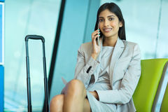 Indian woman smart phone. Pretty indian woman talking on smart phone while waiting at airport Royalty Free Stock Images