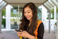Indian woman smiling as she reads a text message Stock Photos