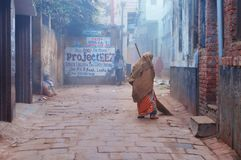 Indian woman sweeps street cold foggy winter morning in Varanasi Stock Photos
