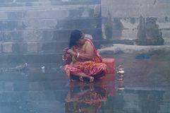 Indian woman taking ritual bath in the river Ganges at cold foggy winter morning. Varanasi Royalty Free Stock Photo