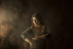 Indian woman throwing colored dust isolated on black background Stock Photos