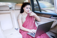 Indian woman uses laptop in car Stock Image