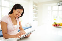 Indian Woman Using Digital Tablet At Home Stock Photo