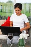 Indian woman using internet. Young Indian Asian woman uses a laptop in a stylish home Stock Photography