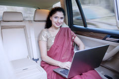 Indian woman using laptop inside car Stock Image
