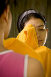 Indian woman using towel over mirro Royalty Free Stock Photo