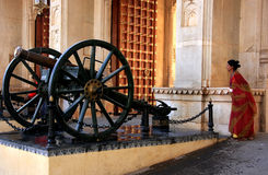 Indian woman walking by Cannons at City Palace complex gate, Udaipur, India Stock Photo