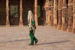 Indian woman walking through courtyard of Quwwat-Ul-Islam mosque Stock Image