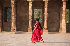 Indian woman walking through courtyard of Quwwat-Ul-Islam mosque Stock Photos
