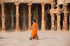 Indian woman walking through courtyard of Quwwat-Ul-Islam mosque Royalty Free Stock Photography
