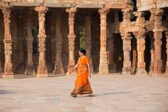 Indian woman walking through courtyard of Quwwat-Ul-Islam mosque Royalty Free Stock Photography
