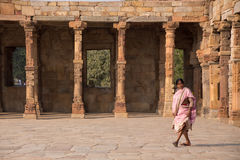 Indian woman walking through courtyard of Quwwat-Ul-Islam mosque Royalty Free Stock Image