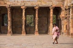 Indian woman walking through courtyard of Quwwat-Ul-Islam mosque Royalty Free Stock Image